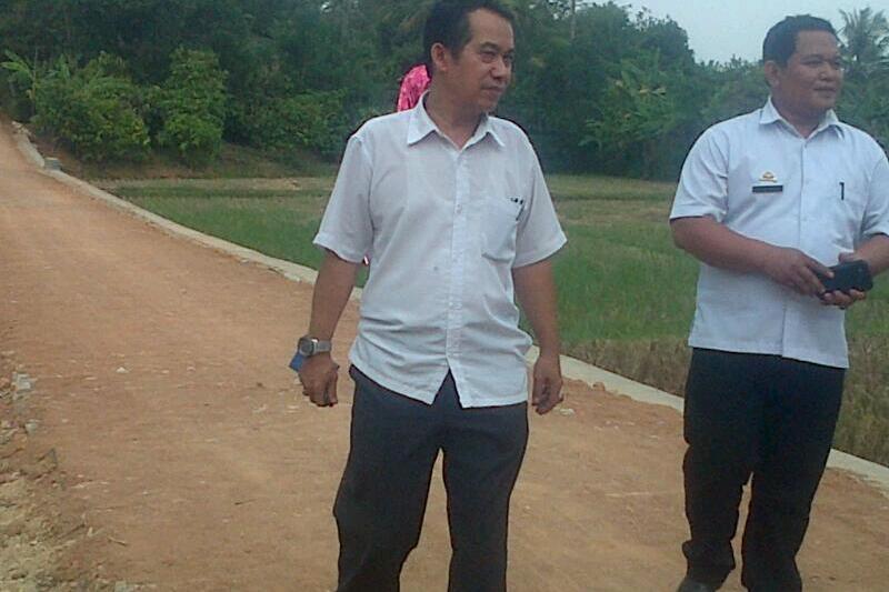 Ketua Tim Monitoring Drs. Edianto (kiri) bersama Sekretaris Pekon Sofianto (kanan) saat meninjau lokasi jalan onderlagh dan TPT di dusun 5. Foto : Sebatin.com.